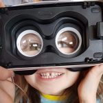 Little kid wearing vr goggles back to front so their eyes are magnified.